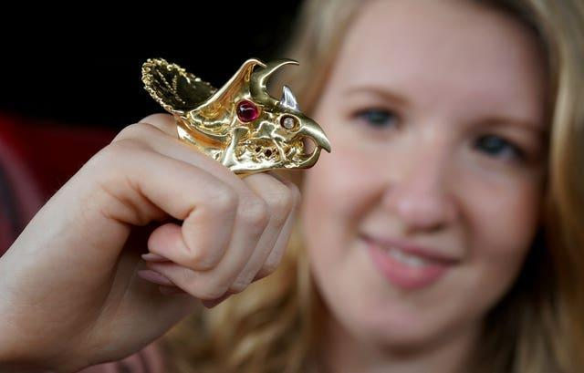 Annabel Winship of Bellmans auction house in West Sussex, wears an 18ct gold ring with diamonds and cabochon rubies designed as the head of a triceratops (Gareth Fuller/PA)