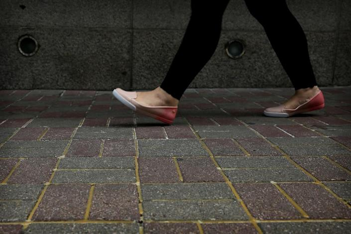 A woman walks over pavement reinforced with glue to prevent the bricks from being dug up and used as projectiles during expected protests in Hong Kong (AFP Photo/Isaac Lawrence)