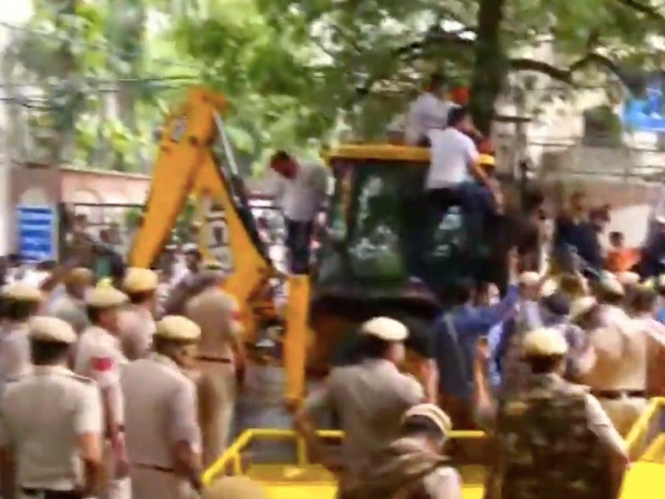 Members of Bharatiya Janata Party (BJP) on a mechanical excavator (JCB) in the lane of Delhi's water body chief Satyendra Jain attempting to disconnect his water connection as part of their protest against 'poor water supply' (Screengrab/Video)