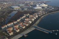 An aerial view from a helicopter shows the Olympic Park (top) under construction and the Olympic Village (bottom) in the Adler district of the Black Sea resort city of Sochi, December 23, 2013. Sochi will host the 2014 Winter Olympic Games in February. Picture taken December 23, 2013. REUTERS/Maxim Shemetov (RUSSIA - Tags: CITYSCAPE BUSINESS CONSTRUCTION SPORT OLYMPICS)