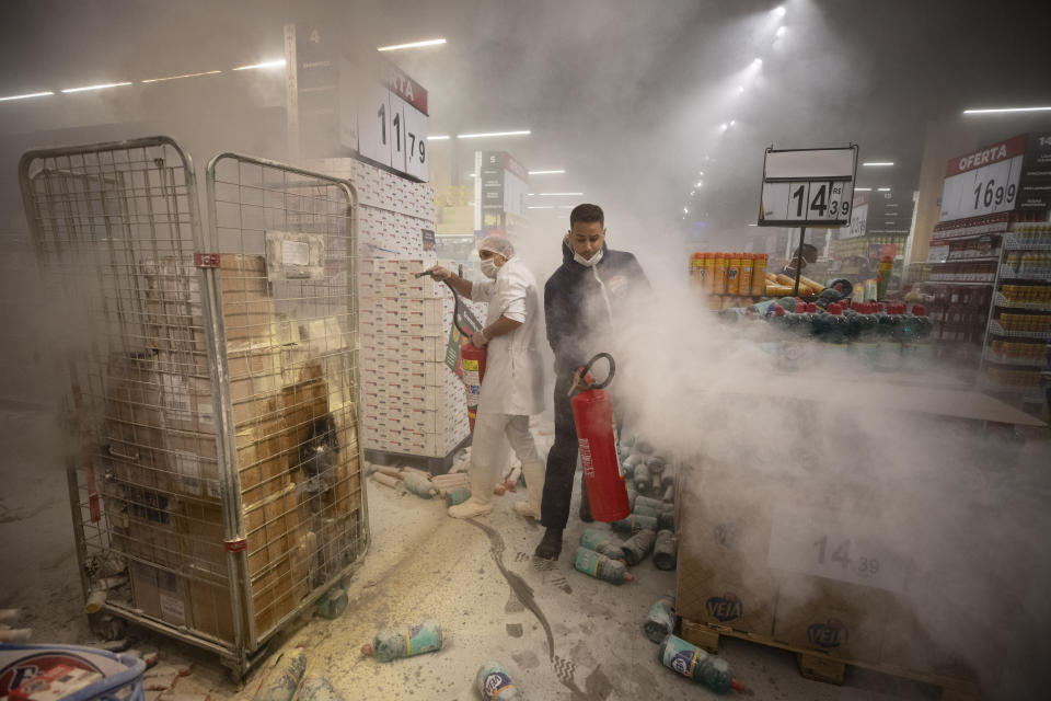 Employees douse a fire set by protesters inside a Carrefour supermarket during a protest against the murder of Black man Joao Alberto Silveira Freitas at a different Carrefour supermarket the night before, on Brazil's National Black Consciousness Day in Sao Paulo, Brazil, Friday, Nov. 20, 2020. Freitas died after being beaten by supermarket security guards in the southern Brazilian city of Porto Alegre, sparking outrage as videos of the incident circulated on social media. (AP Photo/Andre Penner)