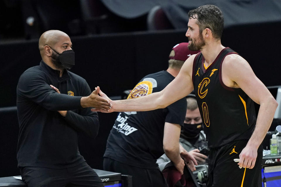Cleveland Cavaliers' Kevin Love, right, is congratulated by coach J.B. Bickerstaff during the second half of the team's NBA basketball game against the Boston Celtics, Wednesday, May 12, 2021, in Cleveland. The Cavaliers won 102-94. (AP Photo/Tony Dejak)