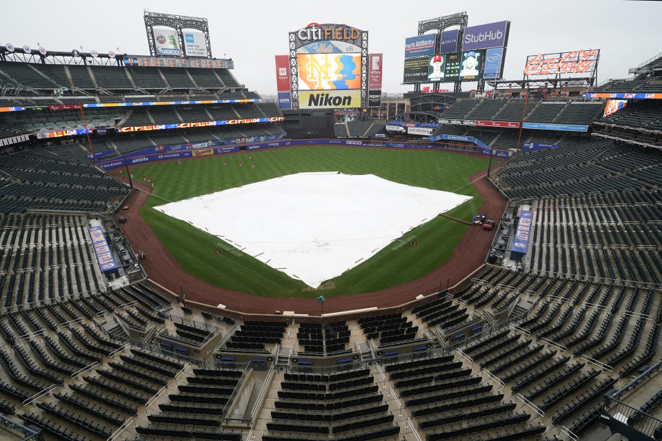 A tarp covers the field after a baseball game between the New York Mets and the Philadelphia Phillies was postponed due to rainy weather, Monday, April 12, 2021, in New York. Monday night's game will be rescheduled as the first game of a single-admission doubleheader, tomorrow, Tuesday, April 13 at 4:10 p.m. (AP Photo/Kathy Willens)