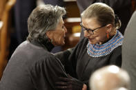 FILE - In this Jan. 20, 20156, file photo, Sen. Barbara Boxer, D-Calif., greets Supreme Court Justice Ruth Bader Ginsburg on Capitol Hill in Washington,before President Barack Obama's State of the Union address before a joint session of Congress.. Ginsburg didn't put on her judge's robe without also fastening something around her neck. Ginsburg called her neckwear collars, or jabots, and they became part of her signature style, along with her glasses, lace gloves and fabric hair ties known as scrunchies.(AP Photo/Jacquelyn Martin)