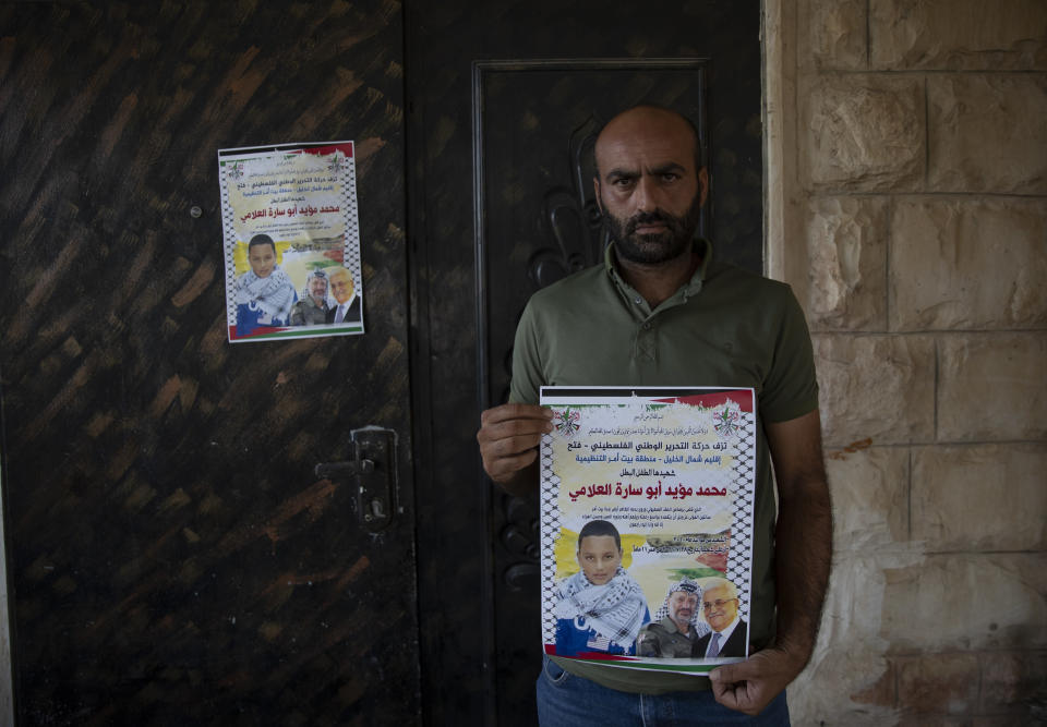 """Palestinian Moayyad al-Alami, father of slain Mohammed al-Alami, 12, carry a poster with picture and name of his son and reads """"Palestinian National Liberation movement, Fatah, offers her hero martyr child,"""" at the family house, in the West Bank village of Beit Ummar, near Hebron, Wednesday, Aug. 4, 2021. (AP Photo/Nasser Nasser)"""