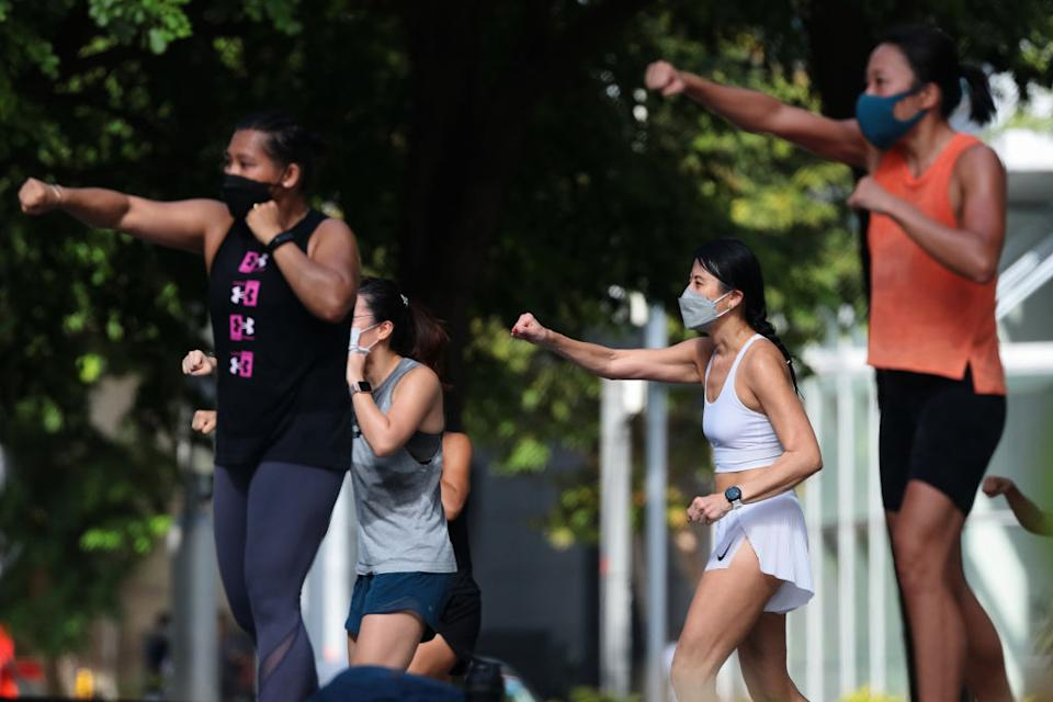 People wearing protective mask engage in an outdoor exercise.
