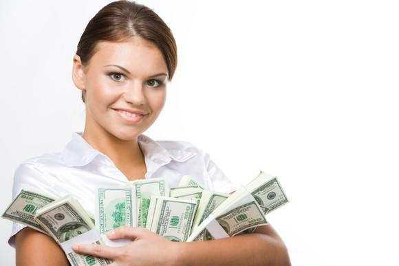 A young smiling woman holding stacks of cash in her arms.