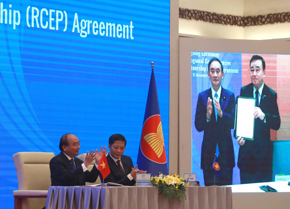 Vietnamese Prime Minister Nguyen Xuan Phuc, left, and Minister of Trade Tran Tuan Anh, right, applaud next to a screen showing Japanese Prime Minister Yoshihide Suga and Minister of Trade Hiroshi Kajiyama holding up signed RCEP agreement, in Haoni, Vietnam. China and 14 other countries have agreed to set up the world's largest trading bloc, encompassing nearly a third of all economic activity, in a deal many in Asia are hoping will help hasten a recovery from the shocks of the pandemic. (AP Photo/Hau Dinh)