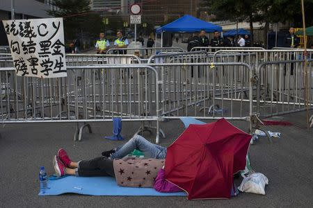 Protesters of the Occupy Central movement sleep in front of metal barricades as police stand guard outside the Government Headquarters early in the morning, while protesters block a main road leading to the financial Central district in Hong Kong October 7, 2014. REUTERS/Tyrone Siu
