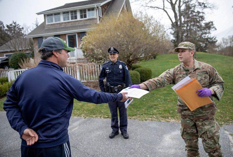 William Randall, right, of the Rhode Island Air National Guard hands an information sheet to New York resident Reha Kocatas, who was self-quarantining at his home in Westerly, R.I.