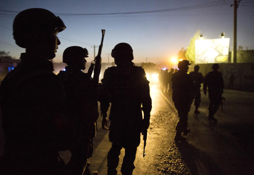 FILE - In this Oct. 18, 2013, file photo Afghan police arrive to secure the area after a car bomb detonated outside an ISAF civilian personnel compound in Kabul, Afghanistan. Police said the assault started at dusk when a car exploded near the gate of a compound, housing contractors from various countries, European diplomatic personnel and United Nations employees. Military contractors got up to half of the $14 trillion spent by the Pentagon since 9/11, a study by Brown University's Costs of War project and the Center for International Policy said Monday, Sept. 13, 2021. The U.S. saw about 7,000 military members die in all post-9/11 conflicts, but nearly 8,000 contractors, another Costs of War study estimates. (AP Photo/Anja Niedringhaus, File)