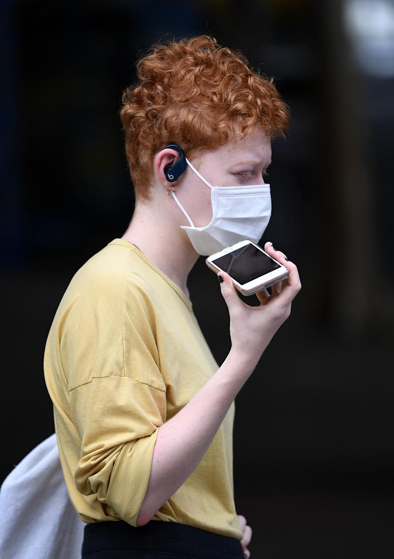 A young woman talks on her phone while wearing a face mask in Brisbane. Source: AAP
