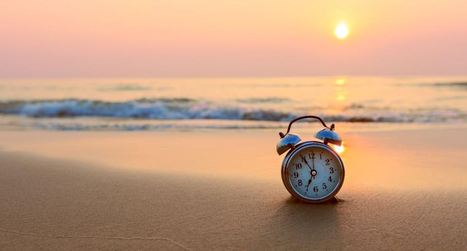 Alarm clock sits on the beach at sunset. Source: Getty Images