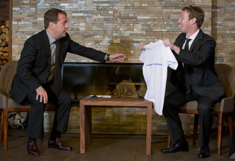 Facebook CEO Mark Zuckerberg, right, presents a T-shirt bearing his Facebook address to Russian Prime Minister Dmitry Medvedev at the Gorki residence outside Moscow, Russia, Monday, Oct. 1, 2012. (AP Photo/Alexander Zemlianichenko, pool)