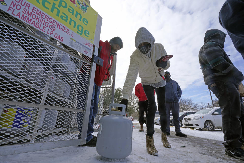 <p>Christine Chapman, center, sets down an empty canister to exchange for a full propane tank from Robert Webster, left, outside a grocery store Tuesday, Feb. 16, 2021, in Dallas. Even though the store lost power, it was open for cash only sales. Chapman said she has been without power for two nights and is using the propane to keep warm. (AP Photo/LM Otero)</p>