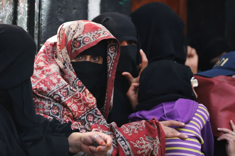 A woman looks on as she queues outside a charity kitchen to get food donations in Sanaa