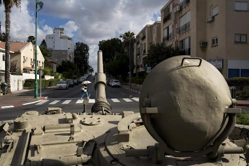 In this photo taken Sunday, Sept. 22, 2013, an Israeli woman crosses a road next to a tank turret placed on a roundabout as a memorial site for Major Toval Gvirtzman who killed in the 1982 Israeli Lebanese war in the northern Israeli town of Hadera. During Israel's 65-year history, the military has fought a half-dozen wars and carried out countless operations, and army service remains compulsory for most Jewish Israelis. Even in peacetime, the military's influence seems to be felt everywhere, with uniformed soldiers seen at bus stations and shopping malls, and war memorials peppering the country. (AP Photo/Oded Balilty)