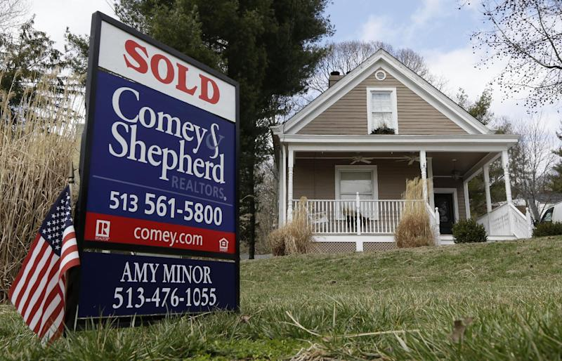In this, Tuesday, March 12, 2013, photo, a sold sign is posted in front of a home for sale in Mariemont, Ohio. Average U.S. rates on fixed mortgages edged up this week but remained near historic lows. Low rates have helped drive the housing market's steady recovery.  (AP Photo/Al Behrman)