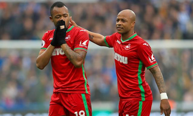 Swansea's Jordan Ayew is consoled by brother André Ayew after being sent off against Huddersfield.