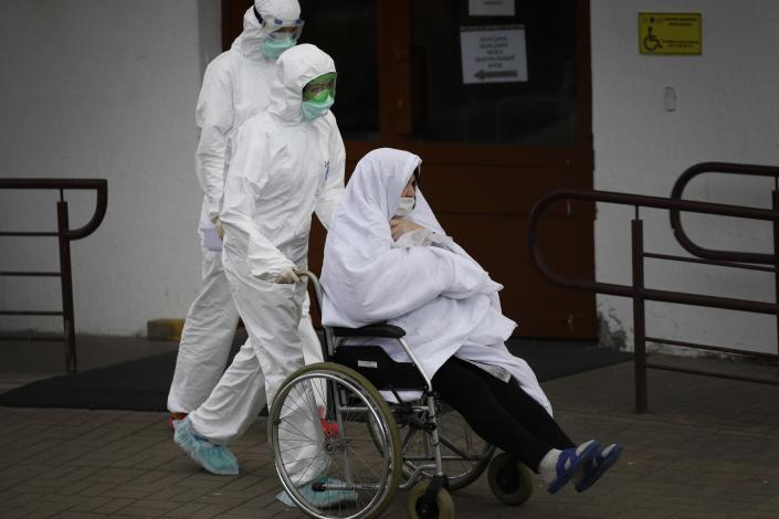 In this photo taken on Tuesday, April 14, 2020, Belarusian healthcare workers wearing face masks and costumes to protect from coronavirus carry a patient in wheelchair outside a hospital in Minsk, Belarus. The 9.5-million Belarus has reported more than 68,500 infections, including 580 deaths, but critics have accused the authorities of manipulating statistics to hide the real number of deaths (AP Photo/Sergei Grits)