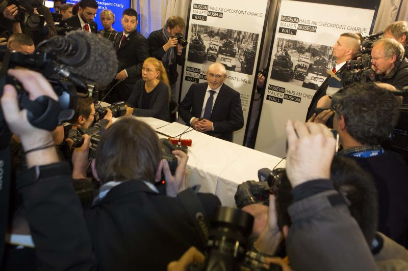 Mikhail Khodorkovsky, center, arrives at his first news conference after his release in Berlin, Sunday, Dec. 22, 2013. The former oil baron and prominent critic of Russian President Vladimir Putin, Mikhail Khodorkovsky, was reunited with his family in Berlin on Saturday, a day after being released from a decade-long imprisonment in Russia. (AP Photo/Markus Schreiber)