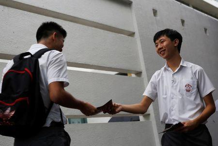 Parco Wong Lok-hang (R), 17-year-old, a secondary school student, hands out leaflets promoting Hong Kong independence in school at the first day of academic year, in Hong Kong, China September 1, 2016. REUTERS/Tyrone Siu