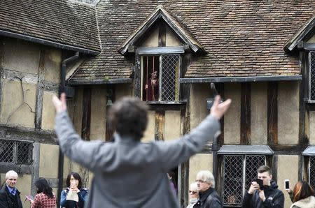 Tourists watch actors perform the Romeo and Juliet window scene at the house where William Shakespeare was born during celebrations to mark the 400th anniversary of the playwright's death in Stratford-Upon-Avon, Britain, April 23, 2016. REUTERS/Dylan Martinez