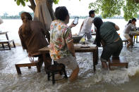 """Customers of the riverside Chaopraya Antique Café react to a boat's wake as they enjoy themselves in the extraordinary high water levels in the Chao Phraya River in Nonthaburi, near Bangkok, Thailand, Thursday, Oct. 7, 2021. The flood-hit restaurant has become an unlikely dining hotspot after fun-loving foodies began flocking to its water-logged deck to eat amid the lapping tide. Now, instead of empty chairs and vacant tables the cafe is as full as ever, offering an experience the canny owner has re-branded as """"hot-pot surfing."""" (AP Photo/Sakchai Lalit)"""