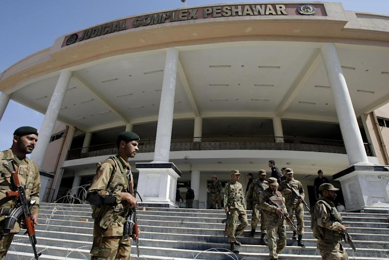 Pakistani army troops gather at a court complex following the gun-battle with militants in Peshawar, Pakistan, Monday, March 18, 2013. A pair of suicide bombers attacked a court complex in the northwestern Pakistani city of Peshawar on Monday, killing at least three people and wounding over two dozen, police said. (AP Photo/Mohammad Sajjad)