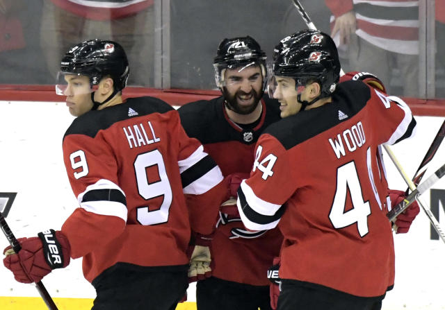 New Jersey Devils right wing Kyle Palmieri (21) celebrates his goal with Miles Wood (44) and Taylor Hall (9) during the third period of an NHL hockey game Tuesday, March 27, 2018, in Newark, N.J. The Devils won 4-3. (AP Photo/Bill Kostroun)