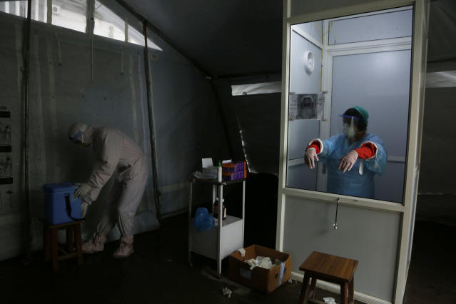"""Nhuja Kaiju, left, of the RNA-16 volunteer group wearing protective suit helps a nurse collect swab samples of patients at a hospital in Bhaktapur, Nepal, Tuesday, May 26, 2020. RNA-16 stands for """"Rescue and Awareness"""" and the 16 kinds of disasters they have prepared to deal with, from Nepal's devastating 2015 earthquake to road accidents. But the unique services of this group of three men and a woman in signature blue vests in the epidemic amount to a much greater sacrifice, said doctors, hospital officials and civic leaders. (AP Photo/Niranjan Shrestha)"""
