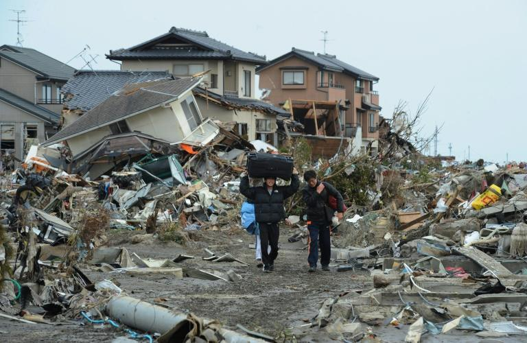 Residents carry belongings from tsunami devastated homes in Natori on March 14, 2011, in the wake of the 9.0-magnitude quake and tsunami which hit the region three days earlier