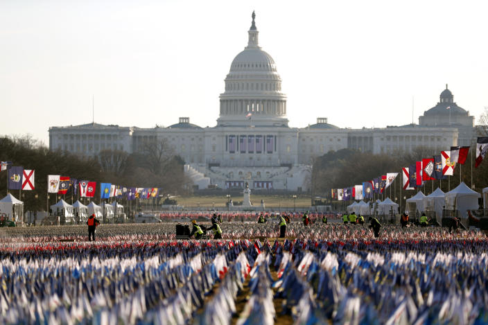 Workers begin to remove a display of flags on the National Mall one day after the inauguration of President Joe Biden, Thursday, Jan. 21, 2021, in Washington. (AP Photo/Rebecca Blackwell)