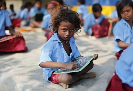 A child whose parents work in a brick kiln attends a class in an open air school at Krishnadevpur village, north of Kolkata, February 11, 2014. REUTERS/Ahmad Masood