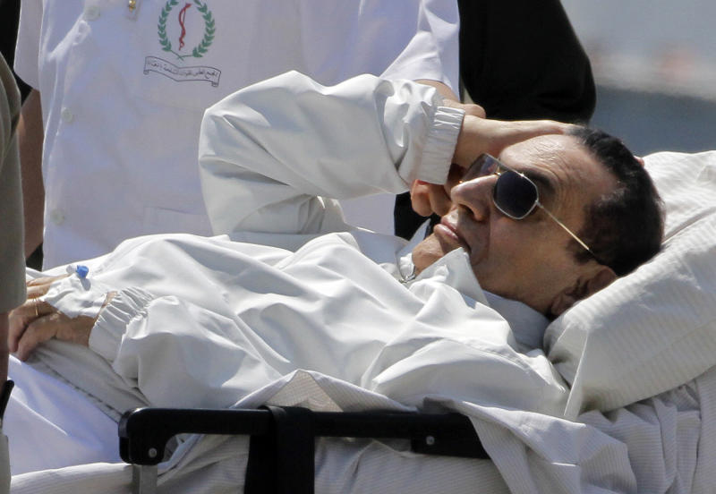 Egyptian medics and army personnel escort former Egyptian President Hosni Mubarak from a helicopter ambulance after it landed at Maadi Military Hospital following a hearing in his retrial in Cairo, Egypt, Saturday, April 13, 2013. Egypt's highest court in January ordered a retrial for Mubarak, for failing to stop the killing of 900 protestors in the 2011 unrest that ousted him, after accepting an appeal against his life sentence, citing procedural failings. (AP Photo/ Amr Nabil)