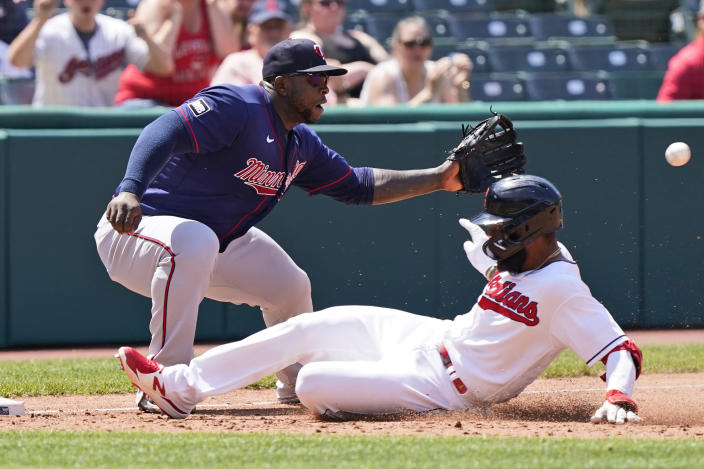 Cleveland Indians' Amed Rosario, right, slides safely into third base for a triple as Minnesota Twins' Miguel Sano waits for the ball in the fifth inning of a baseball game, Sunday, May 23, 2021, in Cleveland. (AP Photo/Tony Dejak)