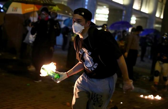 An anti-government demonstrator carries a molotov cocktail during protests at Tsim Sha Tsui, in Hong Kong