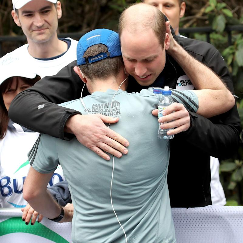 The Duke of Cambridge hugs a runner as he hands out water - Credit: Chris Jackson/PA Wire