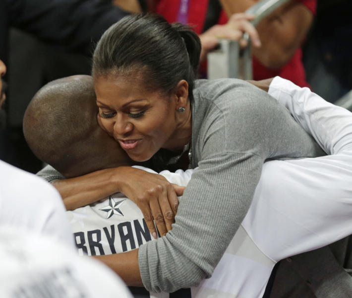 First Lady Michelle Obama hugs USA's Kobe Bryant after Team USA defeated France in a preliminary men's basketball game at the 2012 Summer Olympics, Sunday, July 29, 2012, in London. (AP Photo/Charles Krupa)