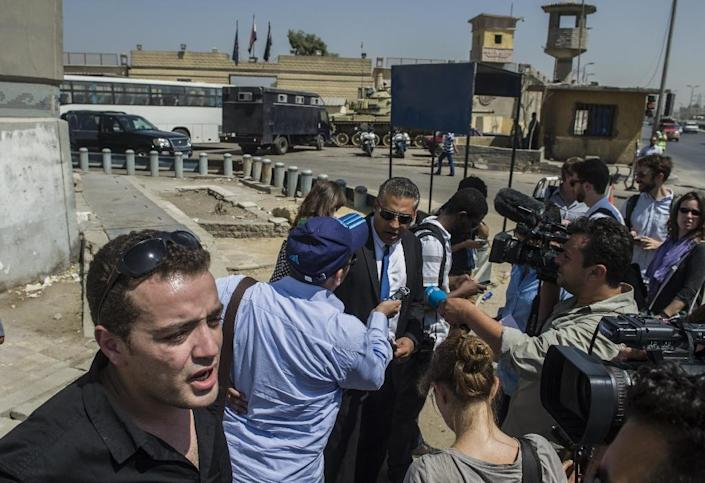 Al-Jazeera journalists Mohamed Fahmy (C) and Baher Mohamed (L), talk to media outside Cairo's Torah prison where their trial was due to take place on July 30, 2015 (AFP Photo/Khaled Desouki)