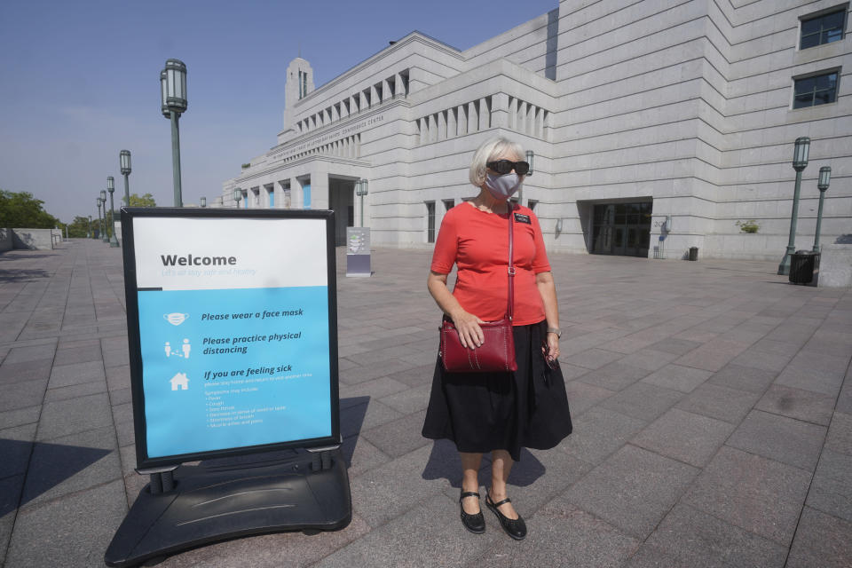 FILE - In this Aug. 26, 2021, file photo, The Church of Jesus Christ of Latter-day Saints church member Rebecca Richards wears a mask outside the The Church of Jesus Christ of Latter-day Saints Conference Center in Salt Lake City. The Church of Jesus Christ of Latter-day Saints has announced that face masks will be required inside temples to limit the spread of COVID-19. Church leaders said Wednesday, Sept. 22, 2021, that masks will be required temporarily in an effort to keep temples open. (AP Photo/Rick Bowmer, File)
