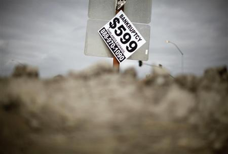 A sign advertising bankruptcy filing is seen hanging off a road sign in San Bernardino