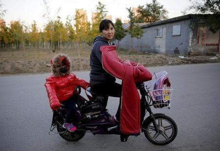 Lv Hongli and her second daughter ride on a bicycle while posing at a migrant workers' village in Beijing