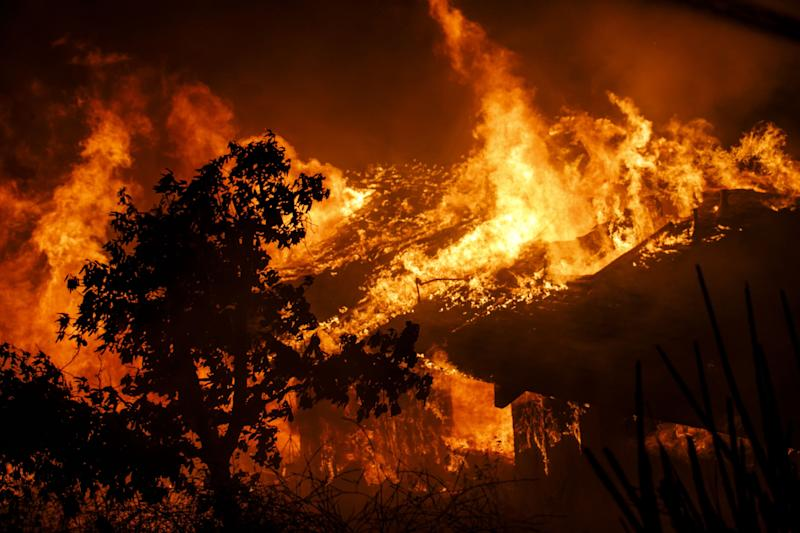 Flamesconsume a home as a brush fire sweeps through Oak View, a community in Ventura County, on Tuesday.