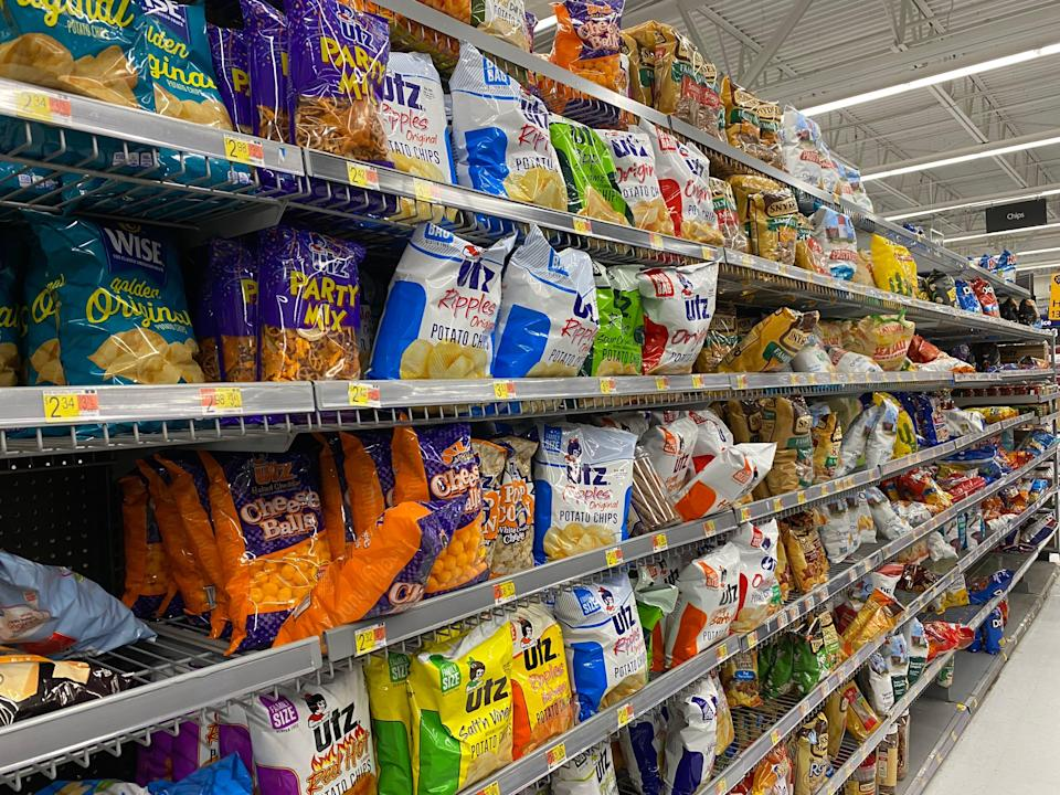 rows and shelving filled with various kinds of chip bags in a walmart