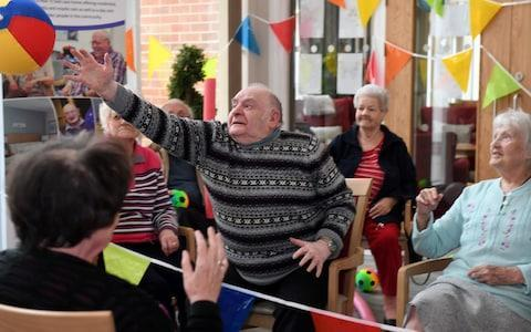 """Old age is often described as a second childhood, and now sports bodies are tapping into that sense of playfulness in later life to encourage more elderly people to exercise. Although activities like volleyball and weightlifting may not seem obvious hobbies for pensioners, sports groups have rewritten their rules to get more older people involved. In a project funded by Sport England, Volleyball England is now running classes where older people can play from their armchairs, using an inflatable ball, and nets made from bunting. Likewise British Orienteering has altered its trails, so that they pass local landmarks or post boxes, to allow the elderly to take part without venturing too far afield. British Weightlifting is also running modified sessions where pensioners are encouraged to lift water bottles and foam bars to keep up their strength. British Weightlifting has adapted its training to suit older people Although the changes may appear infantilising, they have been greeted with enthusiasm by older people. Reenie Boot, 93, of Welwyn Garden City, said:""""I absolutely loved it, so much fun and can't wait for next time to get moving and laughing"""" Sport England, which recently launched its Active Ageing fund to tackle inactivity in the over 55s said it was important to keep fit later in life to prevent illness. Mike Diaper, Executive Director at Sport England said: """"Being active is one of the most important things people can do to maintain health and wellbeing as they age."""" Peter Hart, CEO of British Orienteering added: """"This is the first time we have adapted many of our introductory activities to work with inactive older adults. """"It's my belief that orienteering can offer older adults a fantastic mix of physical and mental exercise by adapting the challenge to suit their abilities."""" It is hoped the new sessions boost health and prevent loneliness Credit: Jane Russell The project is also hoping to tackle loneliness in the elderly. According to the Campaign To End Lon"""