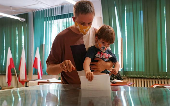 Face masks and first time voters: A parent and child cast their votes in the Polish election - Getty Images Europe