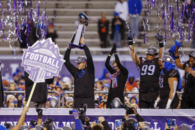 Boise State coach Bryan Harsin holds up the Mountain West Championship trophy, left, as president Marlene Tromp, center, and linebacker Curtis Weaver, right, celebrate. (AP Photo/Steve Conner)