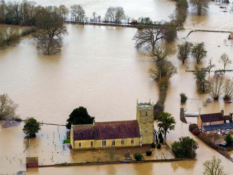 Flood water surrounds a church in Tirley, Gloucestershire, as more rain in northern England could lead to further flooding: PA