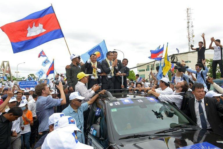 Leader of the opposition Cambodia National Rescue Party Sam Rainsy greets supporters in Phnom Penh on July 19, 2013